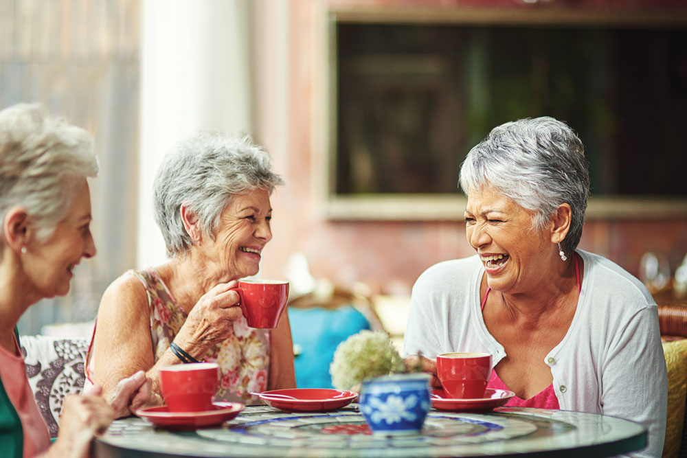 Community Lifestyles: memory care residents laughing together over cups of tea