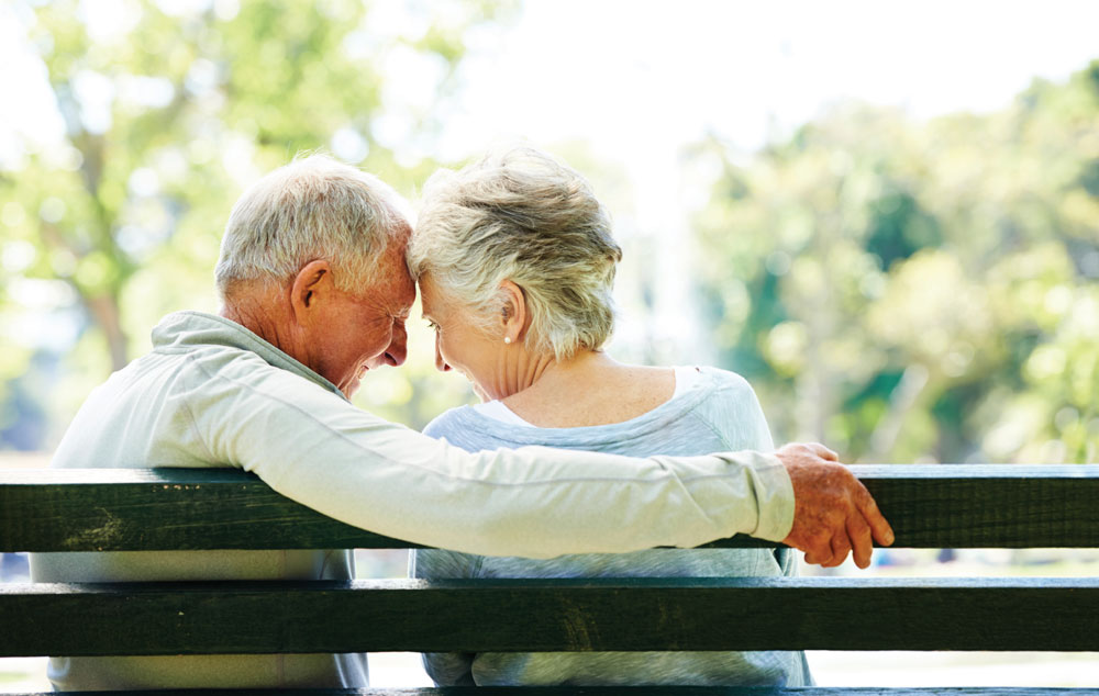 Two residents enjoying romantic moment on park bench in garden at assisted living community.
